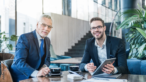 Portrait of two successful businessmen working and sitting on sofa in office lobby