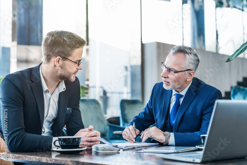 Horizontal shot of young executive showing his business proposal to a senior man sitting in foyer