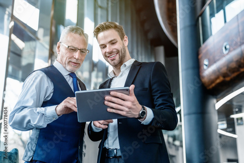 Cheerful young businessman with digital tablet discussing with senior male colleague in office lobby
