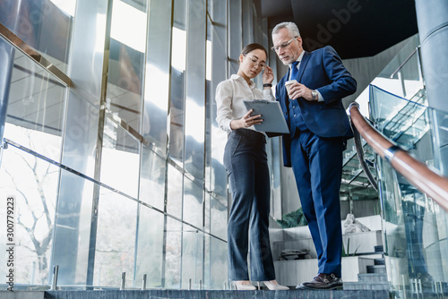 Two business partners holding documents and discussing business plans together while standing at business center stairs