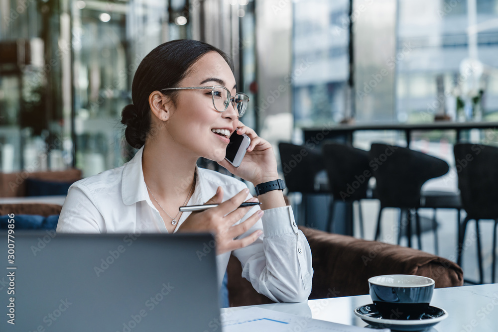 Fototapeta Asian business woman making a phone call and smiling indoor