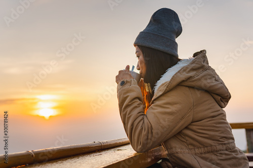 Fototapeta  An Asian woman sits coffee at sunrise on the top of a mountain.