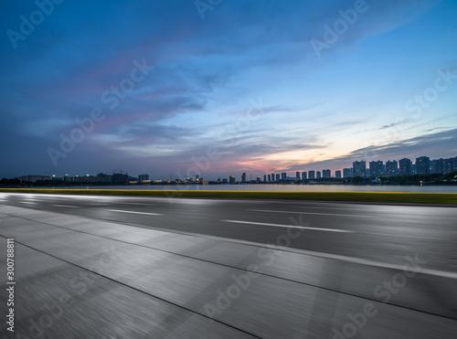 Foto op Plexiglas Grijs Asphalt road and the beautiful urban skyline at sunset