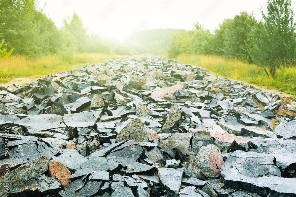 Fototapeta Closeup of broken asphalt on a road in summer.