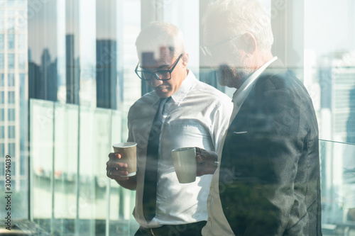 business background of two businessman standing together with hands holding a cu Canvas Print