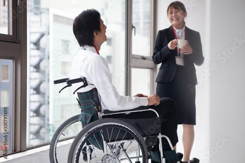 女性社員と談笑する車椅子のビジネスマン Fototapet