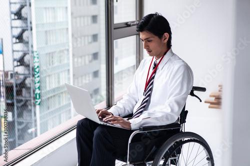 パソコン作業をする車椅子のビジネスマン Fototapeta