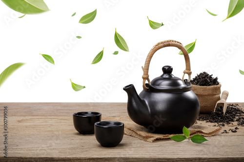 Foto auf Leinwand Tee Cup of hot tea with teapot, flying green tea leaves in the air and dried herbs on the wooden table isolate white background, Organic product from the nature for healthy with traditional