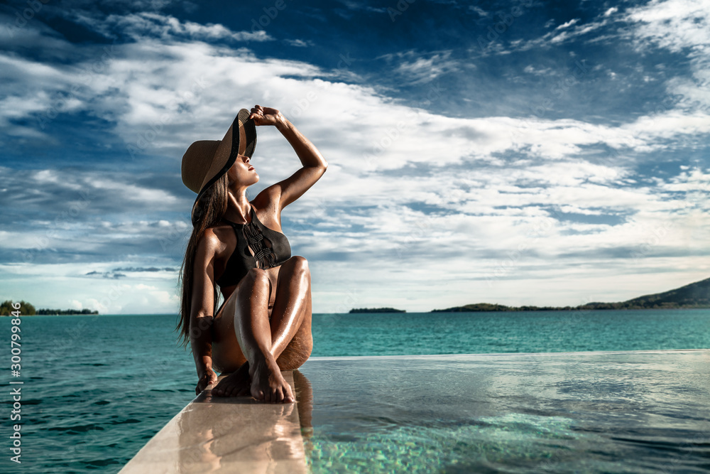 Fototapeta Elegant luxury black swimsuit swimwear model woman with sun hat on infinity pool resort vacation. Europe holiday hotel for wellness spa, hair removal laser legs and body care.