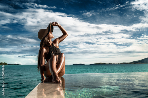 Fototapeta Elegant luxury black swimsuit swimwear model woman with sun hat on infinity pool resort vacation
