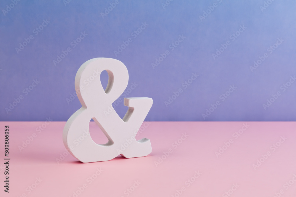 Fototapeta Carved ampersand symbol placed on clean pink purple background with copy space