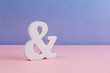 canvas print picture - Carved ampersand symbol placed on clean pink purple background with copy space