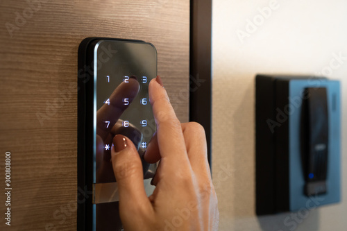 Fotomural Closeup of a woman's finger entering password code on the smart digital touch screen keypad entry door lock in front of the room