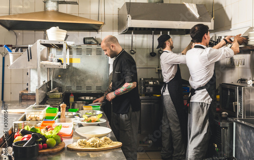 Fototapeta Professional chef cooking in the kitchen restaurant at the hotel, preparing dinner. A cook in an apron makes a salad of vegetables and pizza. obraz