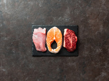 Raw Turkey Breast Fillet, Salmon Steak And Beef Ribeye Steak On Black Slate Board Over Dark Background. Top View Or Flat Lay. Protein Food, Keto, Carnivore, Paleo Diet Concept. Copy Space.