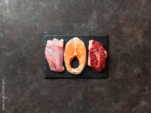 Fotografiet Raw turkey breast fillet, salmon steak and beef ribeye steak on black slate board over dark background
