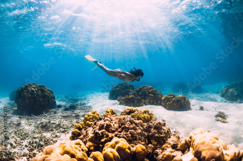 Woman freediver glides over sandy sea with yellow fins in transparent sea Canvas Print