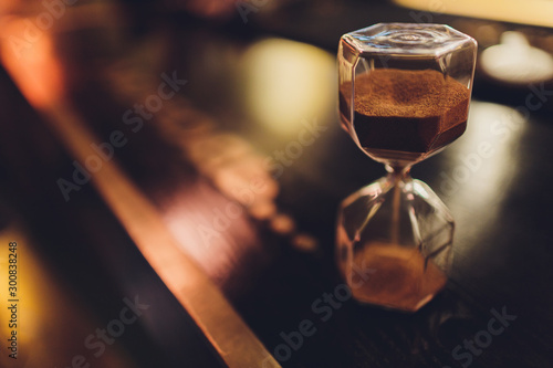 Photo  Hourglass with falling sand inside a glass bulb, passing time or lost time on a dark background with space for text