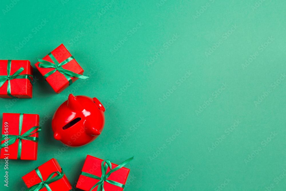 Fototapety, obrazy: Piggy bank and christmas gifts on green background. Saving money and buying Xmas gifts.