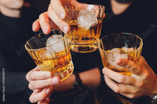 Clinking glasses with alcohol and toasting, party. whiskey ice