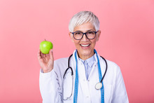 Portrait Of Mature Smiling Female Nutritionist Holding An Apple Isolated. Nutritionist With Healthy Fruit, Juice And Measuring Tape. Dietitian Working On Diet Plan.