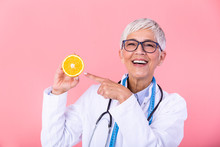 Middle Aged Nutritionist Woman Holding Orange Fruit Happy With Big Smile And Finger Pointing To The Fruit, Nutritionist With Healthy Fruit, Juice And Measuring Tape. Dietitian Working On Diet Plan.