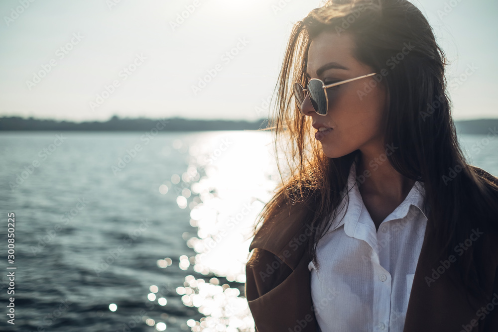 Fototapeta Beautiful Young Stylish Girl in Coat Walking in the Spring Beach at Sunset