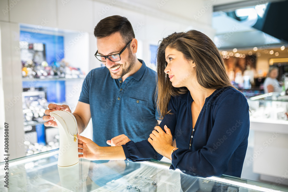 Fototapeta Middle age couple enjoying in shopping at modern jewelry store.