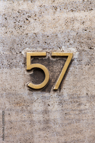 brass number 57 on dirty stone wall Canvas Print