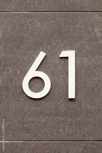 Fotografia  brass number 61 on stone wall