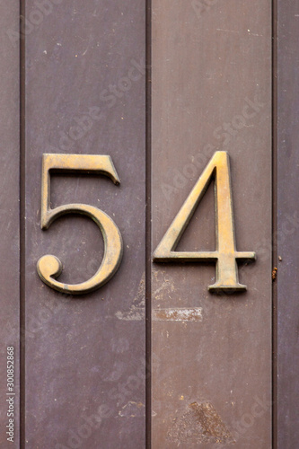 Papel de parede  brass number 54 on stone wall