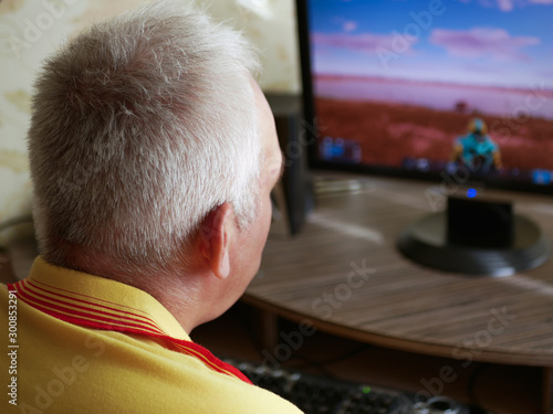 The side-view of a grey haired senior man sitting at the table and playing a bat Canvas Print