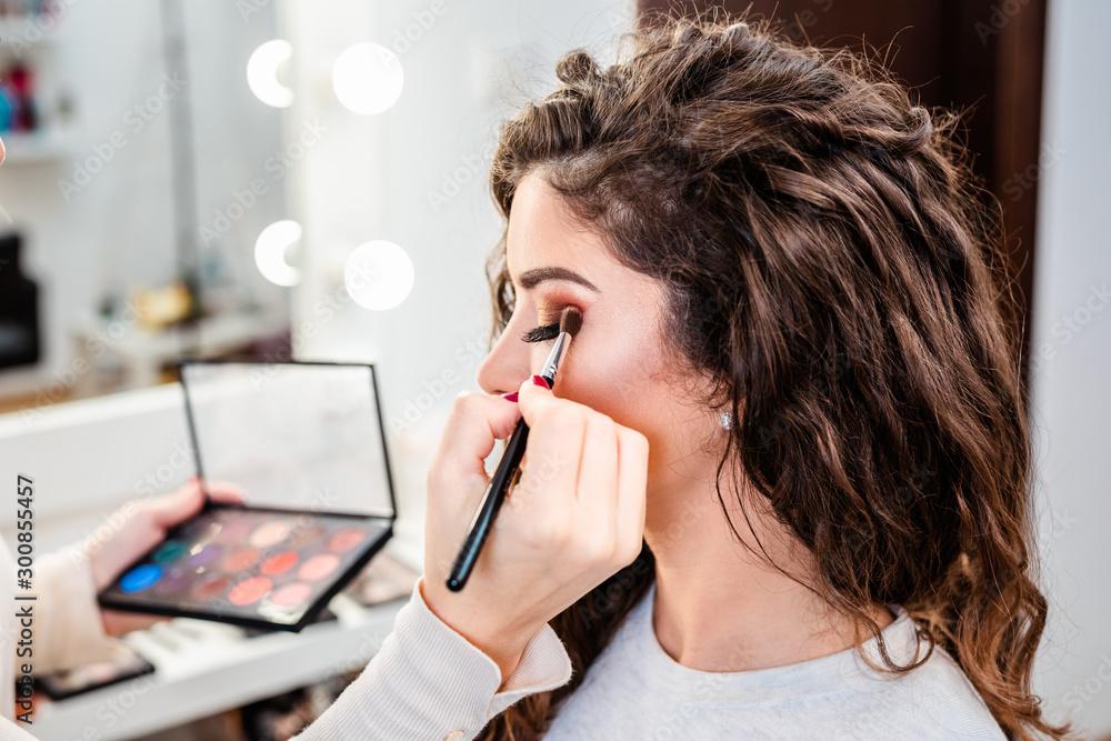 Fototapeta Make up artist applying professional make up of beautiful young woman.