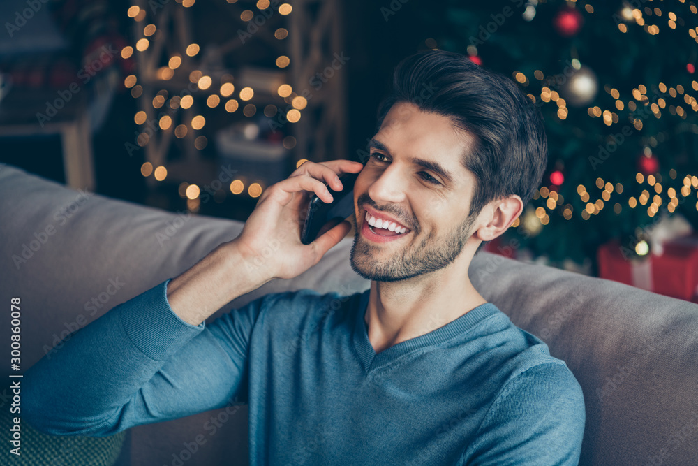 Fototapeta Close up photo of joyful guy speaking cellphone tell congratulations with newyear enjoy christmas atmosphere sit couch in house with bright magic miracle lights