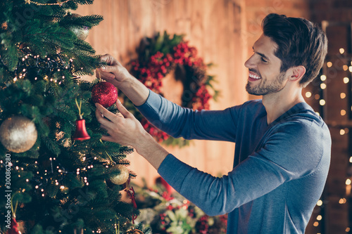 Fotografía  Photo of cheerful bearded brown haired man hanging a toy onto christmas tree smi