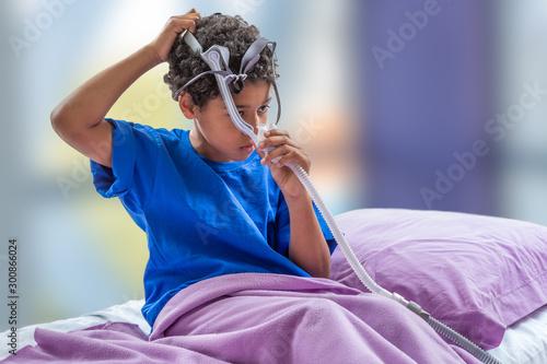 Child suffering from Sleep Apnea, wearing a respiratory mask. Canvas Print