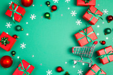 Shopping Trolley With Red Gift Boxes And Copy Space On A Green Background.