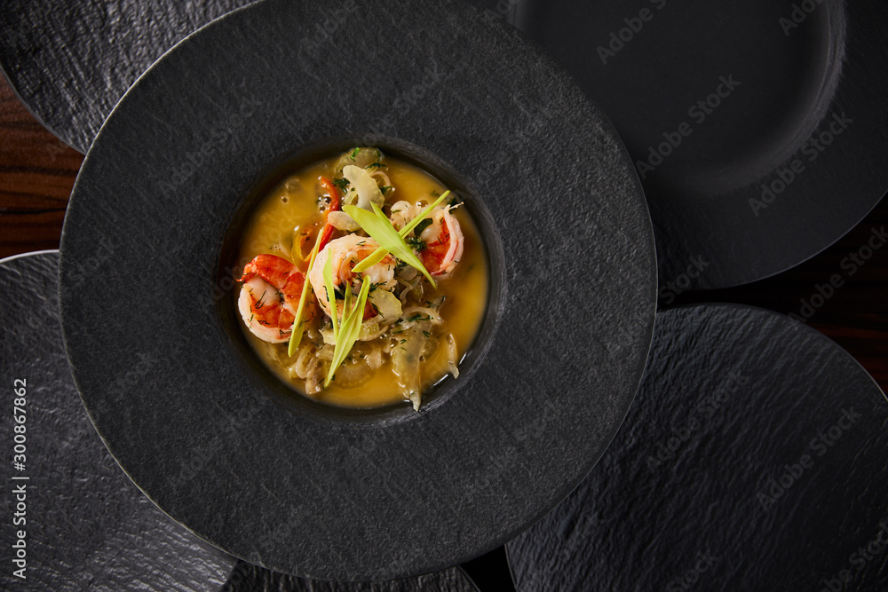 Fototapeta top view of delicious restaurant soup with shrimps in black plate