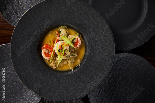 top view of delicious restaurant soup with shrimps in black plate
