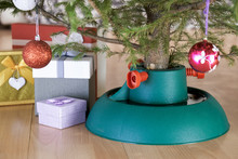 Plastic Christmas Tree Stand With Poured Water Surrounded By Gift Boxes Stands At Home In New Year Eve On The Floor In City Flat