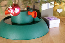 Plastic Christmas Tree Stand With Water Surrounded By Gift Boxes Stands At Home In New Year Eve