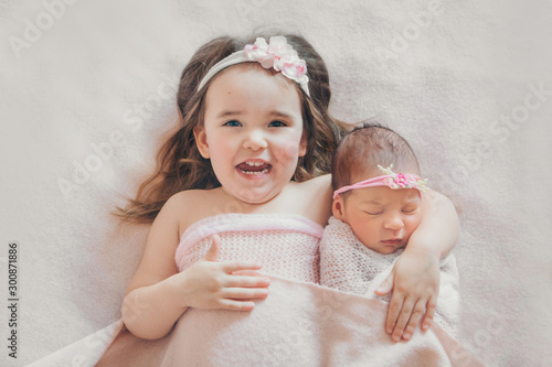 Fototapeta the concept of a healthy lifestyle, the protection of children, shopping - a child with a newborn baby playing together. Happy kids: girls on white background obraz