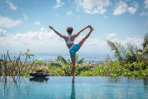 Photo Young woman practicing yoga pose ashtanga hatha asana on the edge of infinity po