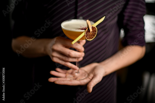 Foto auf Leinwand Alkohol Bartender in the purple shirt serving yellow alcoholic cocktail in the glass with a dried lemon and leaf in the clothespin