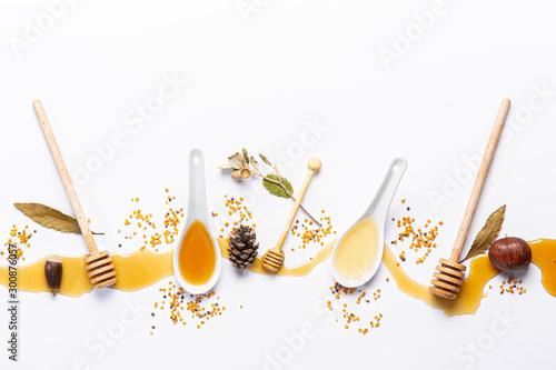 Fotografia white spoons and honey sticks, with spilled honey,