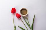 A cup with aromatic black coffee and a beautiful red tulips on a white background