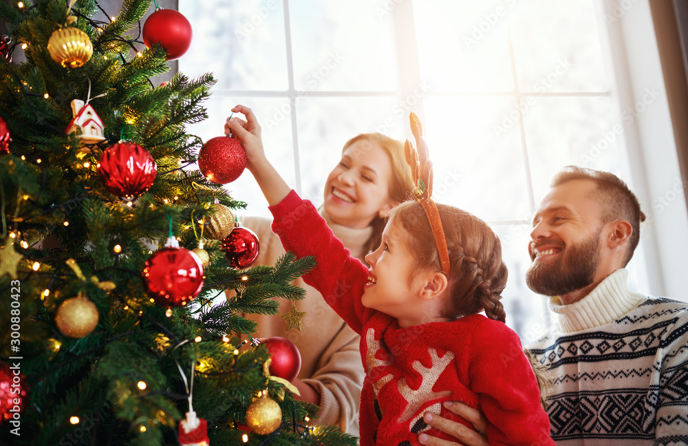 Fototapety, obrazy: happy family mother, father and child daughter decorate Christmas tree  .