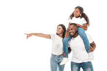 Cheerful African American Woman Pointing With Finger, And Husband Piggybacking Adorable Daughter Isolated On White