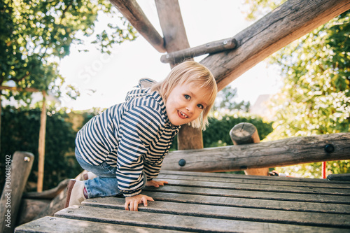 Outdoor portrait of happy toddler girl playing on playground, active child havin Wallpaper Mural