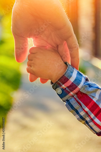 the parent holding the child's hand with a happy background Fototapeta